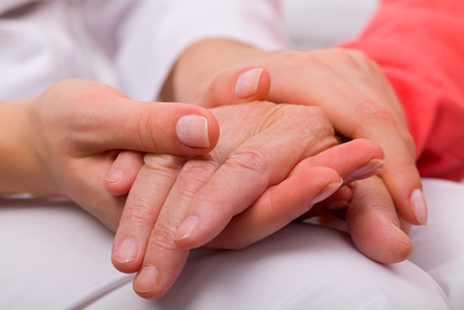Caregiver holding elderly patients hand at home