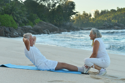Happy Senior couple exercising in summer on  seashore